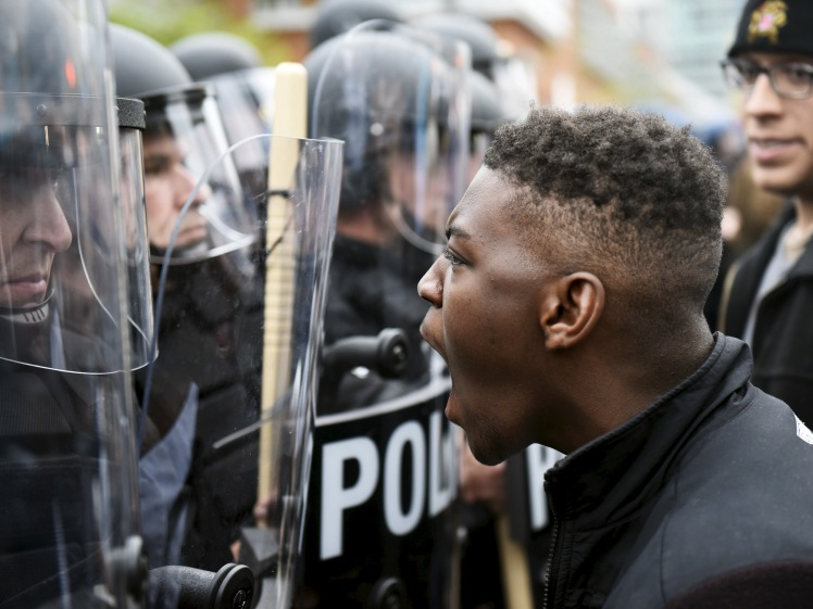 A demonstrator confronts police near Camden Yards during a protest against the death in police custody of Freddie Gray in Baltimore